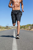 Shirtless man jogging on open road Royalty Free Stock Photos