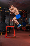 Shirtless man jumping on block Stock Images