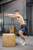 Shirtless man jumping on wooden block stock images