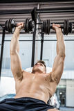 Shirtless man lifting heavy dumbbells on bench royalty free stock photography