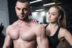 Shirtless man looking at camera with sportive woman near by Royalty Free Stock Photos