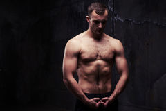 Shirtless man looking at his pumped biceps. Young man with great physique is standing shirtless and looking at his pumped biceps Stock Image