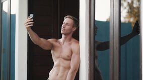 Shirtless man with muscular body makes selfie on phone, shows tongue, funny face