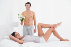 Shirtless man offering a bunch of flowers. Shirtless men offering a bunch of flowers to his girlfriend in bed Stock Photo