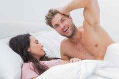 Shirtless man posing next to his sleeping partner. Shirtless men posing next to his sleeping partner in bed Royalty Free Stock Photos