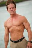 Shirtless man posing by the water Royalty Free Stock Image