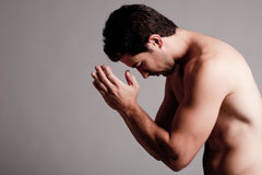 Shirtless man praying Stock Image