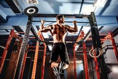 Shirtless man pulling up on horizontal bar. Royalty Free Stock Photos