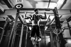 Shirtless man pulling up on horizontal bar. Strong shirtless man pulling up on horizontal bar in a gym Stock Photos