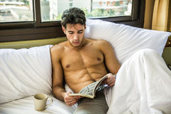 Shirtless man reading a book Royalty Free Stock Images