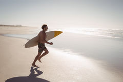 Shirtless man running while holding surfboard at beach Royalty Free Stock Images