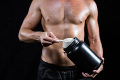 Shirtless man scooping up protein powder Royalty Free Stock Images