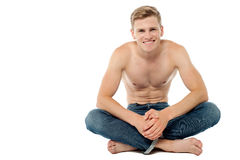 Shirtless man sitting on the floor Stock Image