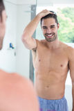 Shirtless man smiling while looking in mirror Royalty Free Stock Images
