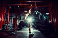 Shirtless man som bläddrar det tunga gummihjulet Royaltyfri Fotografi