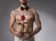Shirtless man standing with flower stock photo