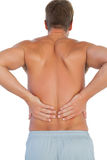 Shirtless man suffering from lower back pain Stock Photography
