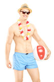 Shirtless man in swimming shorts, holding a beach ball Stock Photos