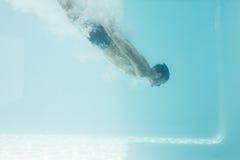 Shirtless man swimming underwater Stock Photo