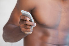 Shirtless man texting on phone Stock Photo