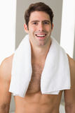 Shirtless man with towel around neck at home. Portrait of a shirtless young man with towel around neck at home Stock Images