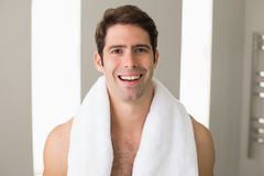 Shirtless man with towel around neck smiling at home Stock Photos