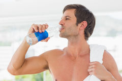 Shirtless man with towel drinking water Stock Images