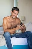 Shirtless Man Using Cell Phone Royalty Free Stock Photography