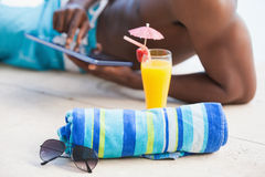 Shirtless man using his tablet pc with towel and sunglasses in foreground Stock Images
