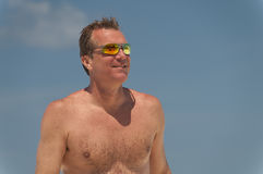 Shirtless man wearing sunglasses at the beach. Stock Photo