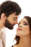 Shirtless man whispering to woman's ear. Royalty Free Stock Images