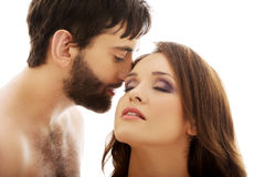 Shirtless man whispering to woman's ear. Stock Photography