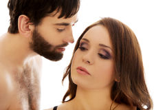 Shirtless man whispering to woman's ear. Handsome shirtless men fondly whispering to woman's ear Royalty Free Stock Photos