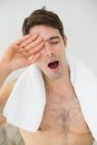 Shirtless man yawning as he rubs his eye Royalty Free Stock Images