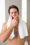 Shirtless man yawning with eyes closed at home Stock Image