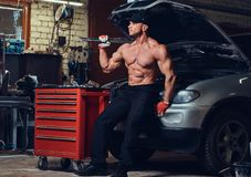 Shirtless mechanic in a garage. A shirtless muscular mechanic with tattoos on his shoulders posing near a car in a garage stock photos