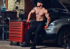 Shirtless mekaniker i ett garage royaltyfri bild
