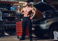 Shirtless mekaniker i ett garage royaltyfri foto