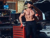 Shirtless mekaniker i ett garage arkivbilder