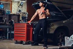 Shirtless mekaniker i ett garage royaltyfria foton