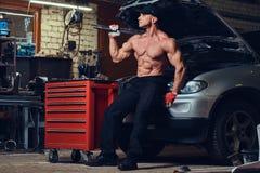 Shirtless mekaniker i ett garage fotografering för bildbyråer