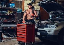 Shirtless mekaniker i ett garage arkivbild