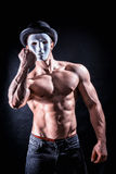 Shirtless muscle man with creepy, scary mask. Being aggressive and violent, on black background royalty free stock photography
