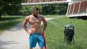 Shirtless muscle man jogging on pathway stock video