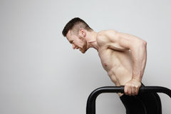 Shirtless muscular athlete doing push-up on push up bars. Stock Photo