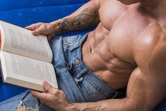 Muscular bodybuilder man reading book stock photo