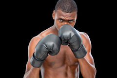 Shirtless muscular boxer in defensive stance. Portrait of a shirtless muscular boxer in defensive stance over black background Stock Photo