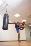 Shirtless muscular boxer kicking punching bag in gym Royalty Free Stock Image
