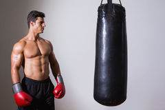 Shirtless muscular boxer looking at punching bag Royalty Free Stock Photo