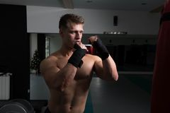 Shirtless Muscular Boxer With Punching Bag In Gym stock photography